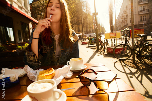 A girl sitting with coffee in a cafe of Berlin
