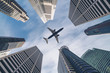 canvas print picture - Airplane flying over city business buildings, high-rise skyscrapers