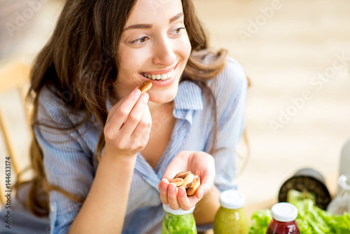 Fotografía  Closeup view from above of a woman eating brasil nuts with healthy food on the b