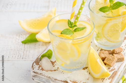 Carta da parati Cold refreshing summer drink with lemon and mint on wooden background