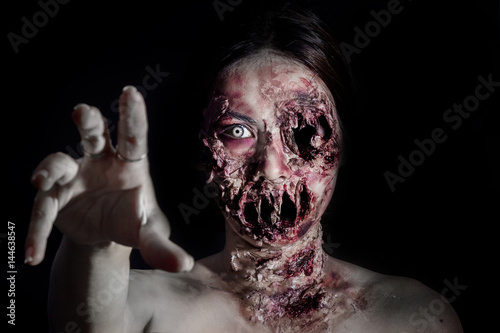 Foto horrible scary zombie girl on black background with copyspace