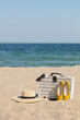 Summer vacation at sea. White wicker suitcase and women's accessories and shoes on the beach.