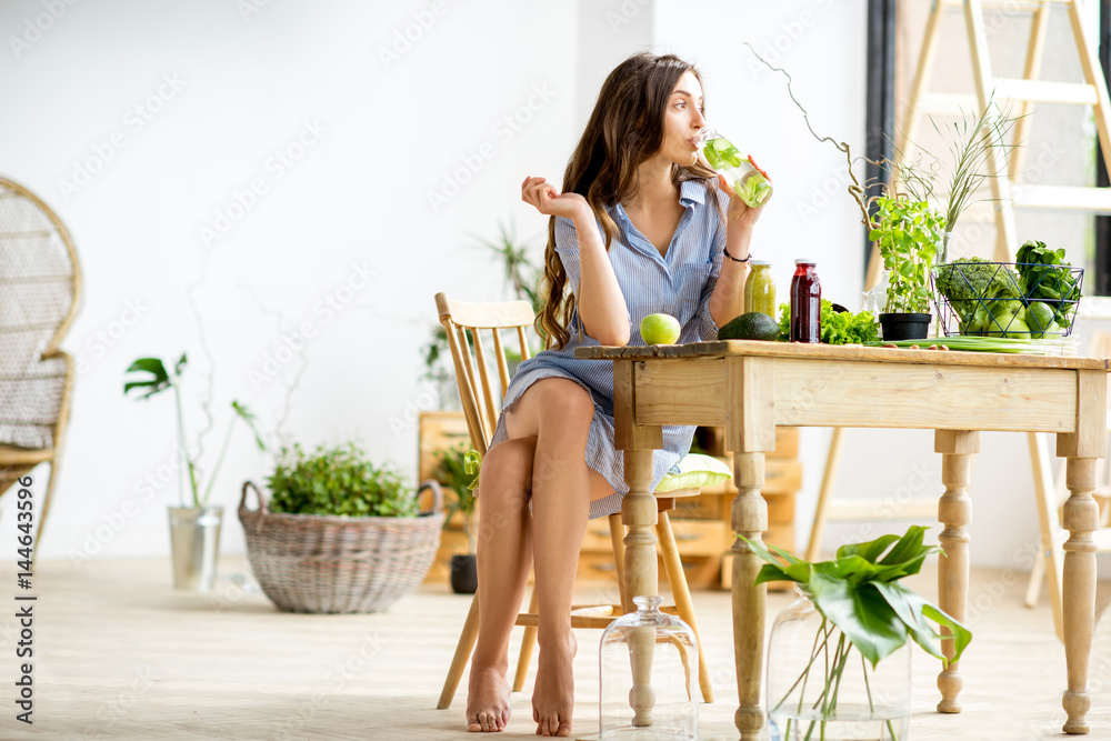 Fototapeta Beautiful woman sitting with healthy green food and drinks at home. Vegan meal and detox concept