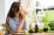 Leinwandbild Motiv Beautiful woman sitting with drinks and healthy green food at home. Vegan meal and detox concept