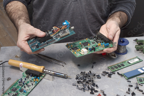 Obraz Pracownik w serwisie elektrycznym podczas pracy. Naprawa sprzętu komputerowego. Naprawa modemu. Wymiana kondensatora. - fototapety do salonu