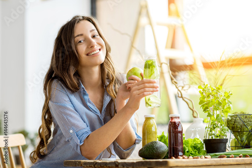 Fotomural Beautiful happy woman sitting with drinks and healthy green food at home