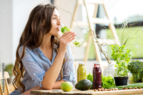 Fotografía Beautiful woman sitting with drinks and healthy green food at home