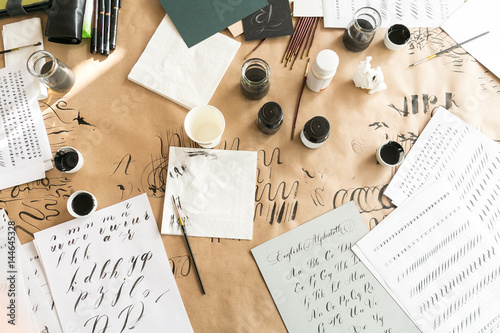 Obraz Calligraphy sheets, nibs, paper, ink and pens on a kraft background. Lettering calligraphy workshop. Letters of the English alphabet written with a paint brush. Concept hobby. top view, flat lay. - fototapety do salonu