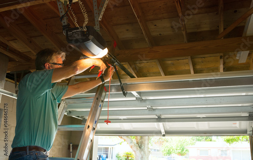 Photo Professional automatic garage door opener repair service technician man working on a ladder at a home residential location making adjustments and fixing it while installing it