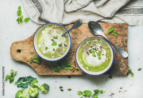 Spring detox broccoli green cream soup with mint and coconut cream in bowls on rustic wooden board over marble background, top view. Clean eating, dieting, vegan, vegetarian, healthy food concept