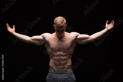 Athletic handsome man fitness-model is showing six pack abs. isolated on black background with copyspace