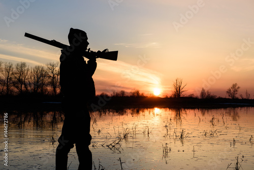 Poster Jacht Silhouette of a hunter at sunset in the water with a gun.