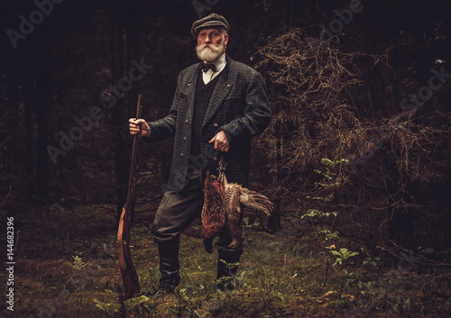 b65e698735590 Senior hunter with a shotgun and pheasants in a traditional shooting  clothing