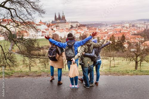 Naklejka premium Widok z tyłu grupy ludzi przytulających się w parku w Pradze na wiosnę. Koncepcja podróży z przyjaciółmi