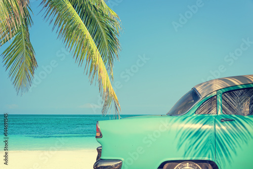 Classic car on a tropical beach with palm tree, vintage process Canvas Print