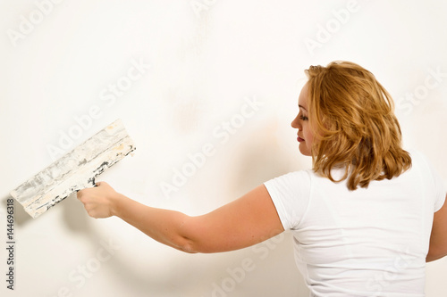 Fotografie, Obraz  Young woman plastering the wall.