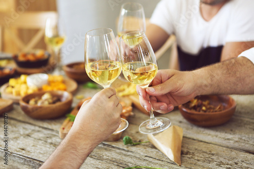 Hands with white wine glasses