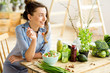 Leinwanddruck Bild - Young and happy woman eating healthy salad sitting on the table with green fresh ingredients indoors