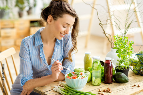 Cuadros en Lienzo Young and happy woman eating healthy salad sitting on the table with green fresh
