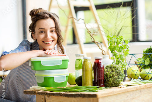 Fotografía  Portrait of a young smiling woman with green lunch boxes indoors