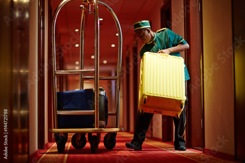 Hotel servant taking out suitcase with baggage from hotel room Tapéta, Fotótapéta