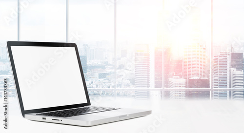 Photo  Laptop on table in office with panoramic view of modern downtown skyscrapers at