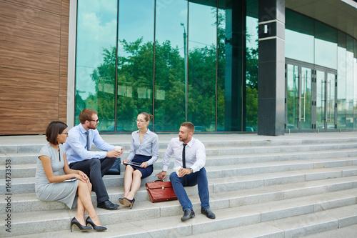 Foto  Gruppe junge Geschäftsleute, die auf Schritten außerhalb des modernen Bürogebäud