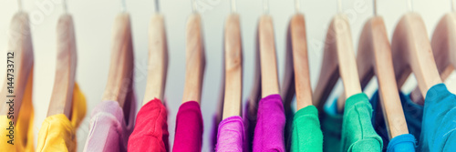 Obraz Banner horizontal crop for text background of clothing rack. Clothes for women hanging on hangers in home closet or shopping mall for store sale concept. Colorful selection of t-shirts. - fototapety do salonu