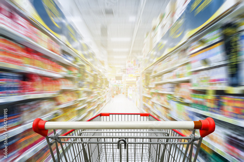 Supermarket aisle with empty red shopping cart Wallpaper Mural