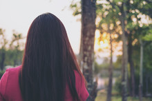 A Woman Standing And Turning Her Back In Green Nature And Light Of Sunset Background