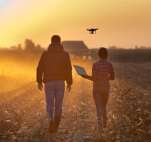 Farmers With Drone On Field