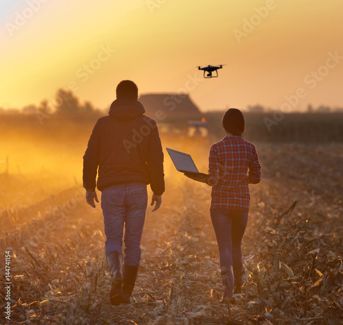 Farmers with drone on field Wall mural