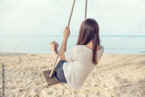 Fototapeta Młoda kobieta relaksuje na huśtawkach w plaży, tylny widok, wolności lato.