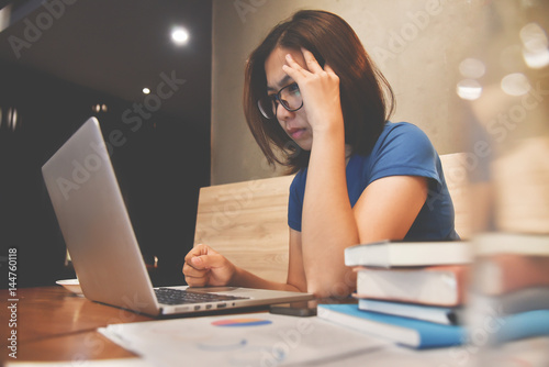 Fotografie, Obraz  Stressed of Asian eyeglasses Woman with laptop and graph financial diagram documents on wooden table