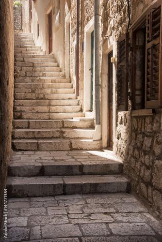 Light pours down a steep narrow Dubrovnik alleyway, Croatia