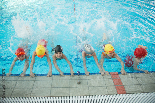 Fotografía  happy children kids group at swimming pool class learning to swim