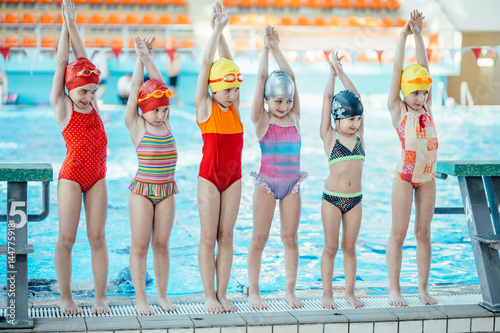 Instructor and group of children doing exercises near a swimming pool Slika na platnu