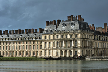 Fototapeta na wymiar Pond and buildings of Fontainebleau Palace in France.