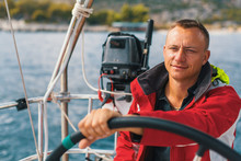 Happy Sailor At The Helm Of His Sailing Yacht.