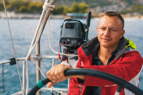 Cadres-photo bureau Voile Happy sailor at the helm of his sailing yacht.