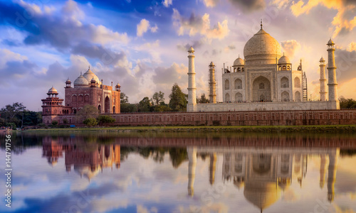 Poster Artistic monument Taj Mahal with a vibrant sunset sky on the banks of river Yamuna. Taj Mahal is a white marble mausoleum designated as a UNESCO World heritage site at Agra, India.