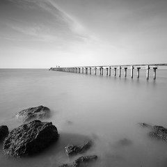 Fototapeta Morze Long exposure shot of seascape with long jetty at background in black and white.