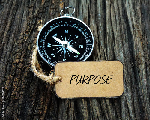 Compass and paper tag written with PURPOSE on wooden background. Wallpaper Mural
