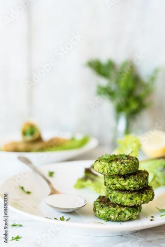 Fotografía  falafel verdi e salsa tahini su piatto bianco; erbe aromatiche e involtini farci