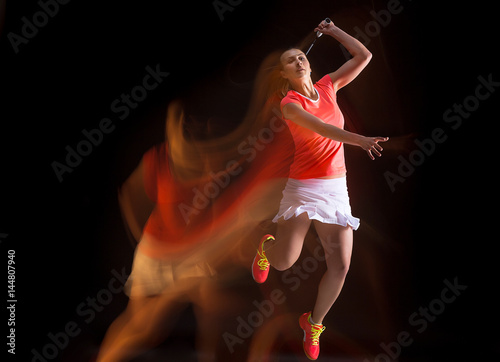 Obrazy Badminton   young-woman-playing-badminton-over-black-background