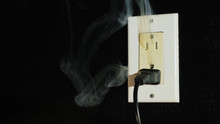 Fire In A Dual-socket US Type. Streams Of Black Smoke Come From The Outlet. Danger To Life And Health