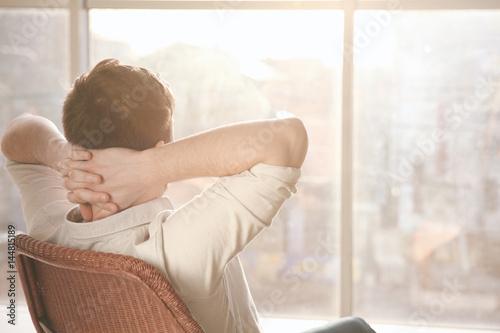 Heureux jeune homme assis sur une chaise près de la grande fenêtre Poster Mural XXL