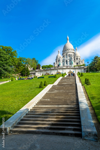 Photo  Sacre Coeur Basilica in Paris at day with blue bright sky and green grass and blooming trees