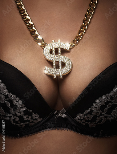 Fotografia, Obraz  Close up of female bust with golden, shiny dollar necklace