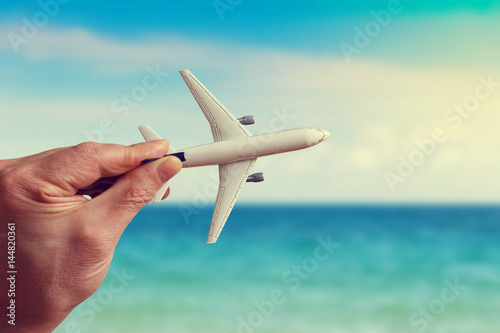 Fotografie, Obraz  Human hand holding model airplane against the background of the sea landscape